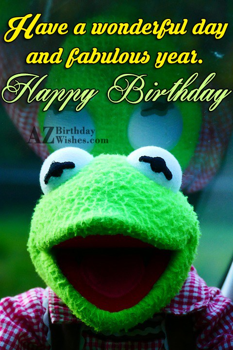 Happy birthday with frog toy in the background - AZBirthdayWishes.com